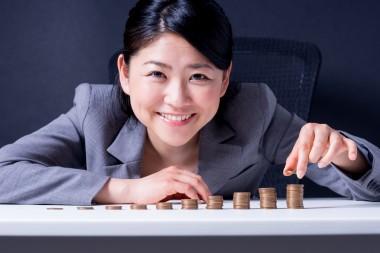 10円玉を積み上げる女性