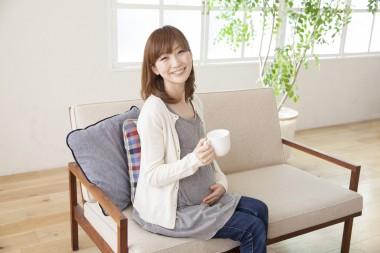 コーヒーカップを持つ妊婦