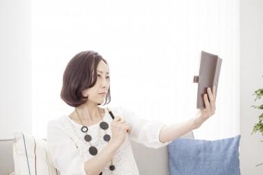 ソファーに腰かけ手帳を持つ女性