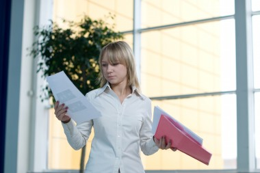 Attractive young businesswoman with folder and paper in office lobby
