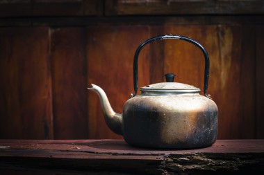 Old aluminium kettle on wood background in vintage