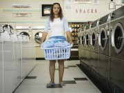 Full view of woman with basket of clothes in laundromat