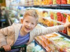 smiling positive boy grocery shopping at the supermarket sitting in the cart helping his mother