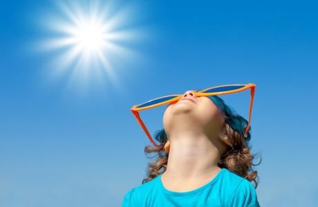 サングラスを付けて太陽を見る子供
