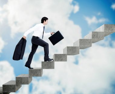 Young businessman climbing grey stairs on sky background