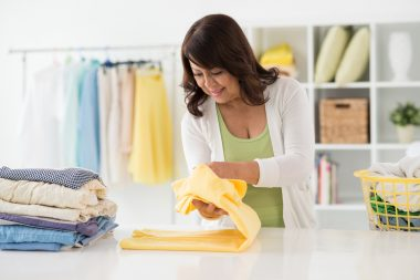 Housewife folding freshly washed shirts