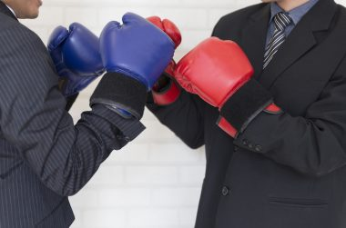 businessman in suit with red and blue boxing gloves punching each other
